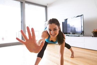 Divorced woman working out at home to save money after divorce